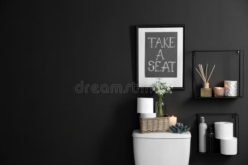 Decor elements, necessities and toilet bowl near black wall, space for text. Bathroom. Interior royalty free stock photography