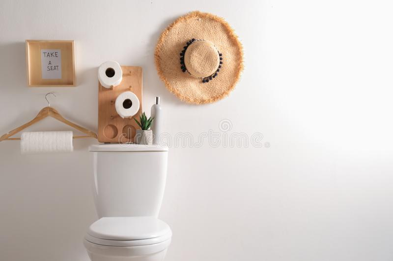 Decor elements, necessities and toilet bowl near white wall. Bathroom interior. Decor elements, necessities and toilet bowl near white wall, space for text stock image