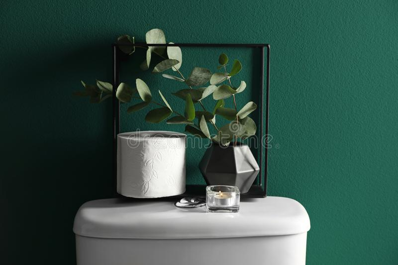 Decor elements and paper roll on toilet tank near  wall. Decor elements and paper roll on toilet tank near green wall. Bathroom interior royalty free stock photography