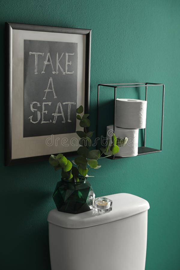 Decor elements, paper rolls and toilet bowl near green wall. Bathroom. Interior royalty free stock photos