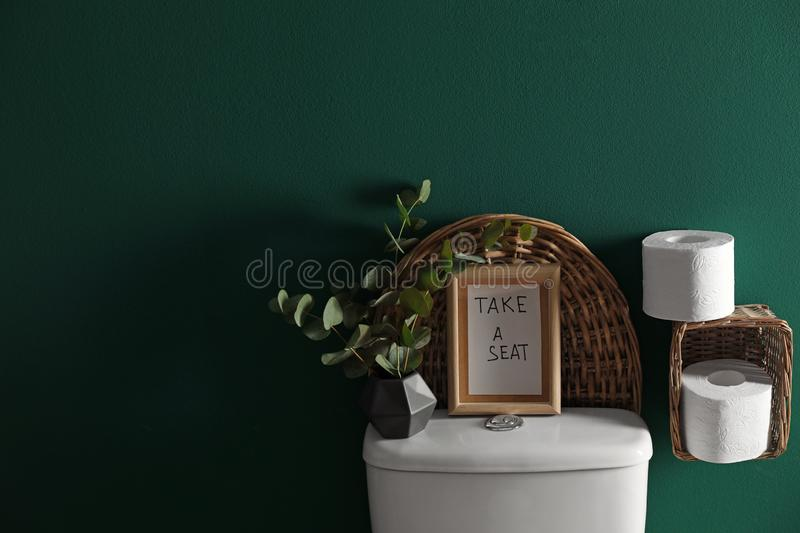 Decor elements, paper rolls and toilet bowl near green wall. Bathroom interior. Decor elements, paper rolls and toilet bowl near green wall, space for text stock images