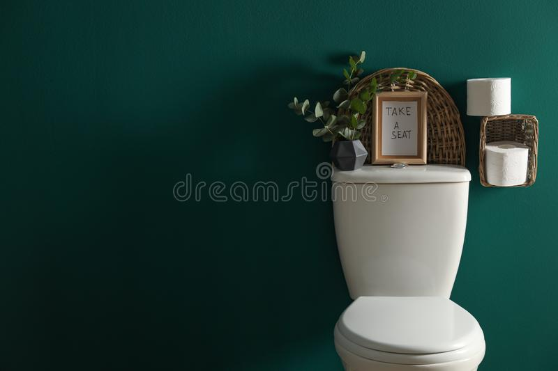 Decor elements, paper rolls and toilet bowl near green wall, space for text. Bathroom. Interior stock photo