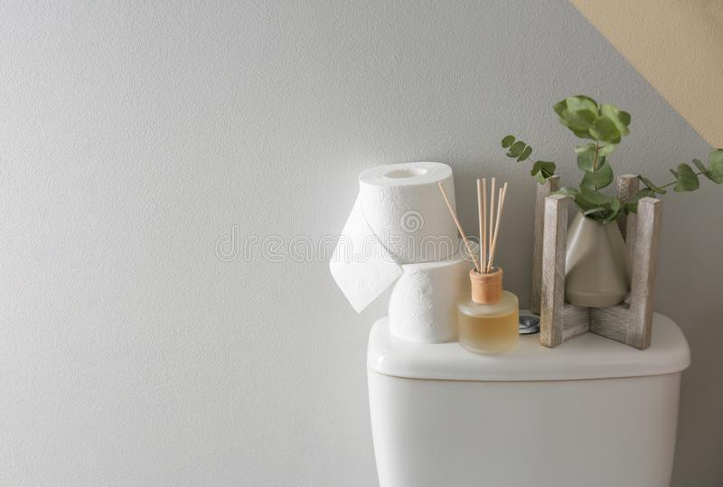 Decor elements and paper rolls on toilet tank near color wall, space for text. Bathroom stock photo