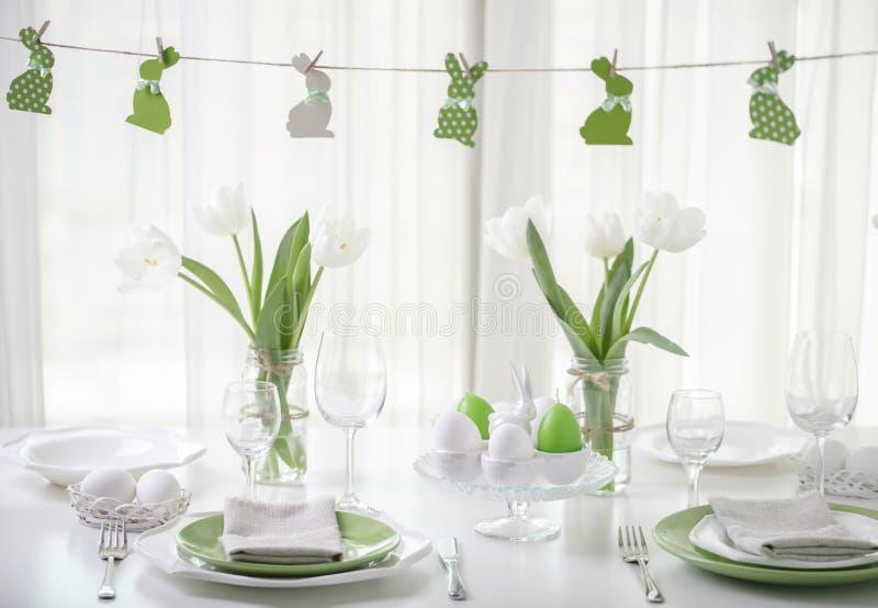 Decor en lijst het plaatsen van de Pasen-lijst met witte tulpen en schotels van groene en witte kleur Pasen-decor in de vorm van stock fotografie