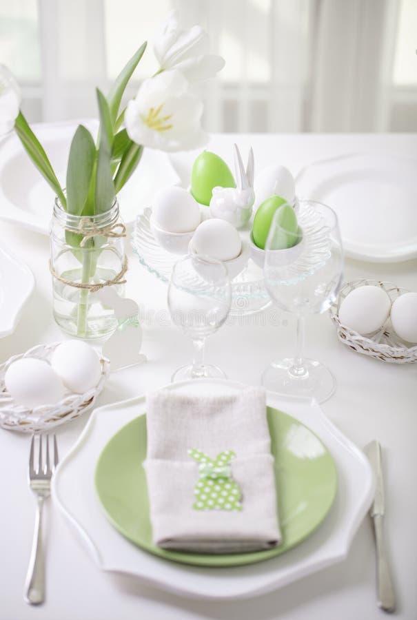 Decor en lijst het plaatsen van de Pasen-lijst met witte tulpen en schotels van groene en witte kleur Pasen-decor in de vorm van royalty-vrije stock foto