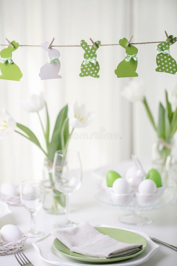 Decor en lijst het plaatsen van de Pasen-lijst met witte tulpen en schotels van groene en witte kleur Pasen-decor in de vorm van stock foto's