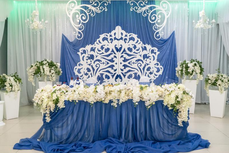 Decor on the wedding table with blue screen in the background, wedding decoration of the main table of the bride royalty free stock photo