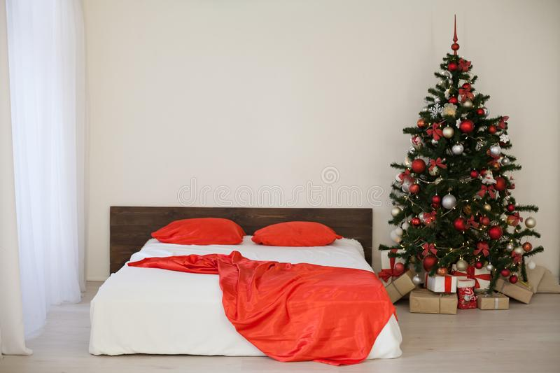 Decor white bedroom with Christmas tree Christmas gifts Red. 1 royalty free stock photo