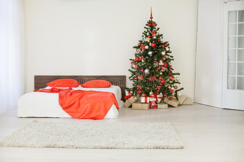 Decor white bedroom with Christmas tree Christmas gifts Red. 1 royalty free stock photography