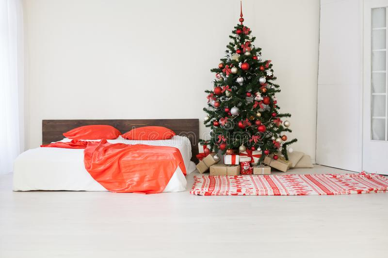 Decor white bedroom with Christmas tree Christmas gifts Red. 1 stock photography