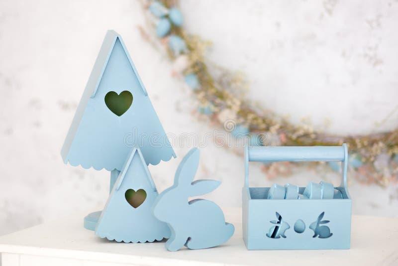 A decoração à moda da casa no azul é uma cesta de madeira, umas caixas de aninhamento decorativas e um coelho bonito Decora??es d imagens de stock royalty free