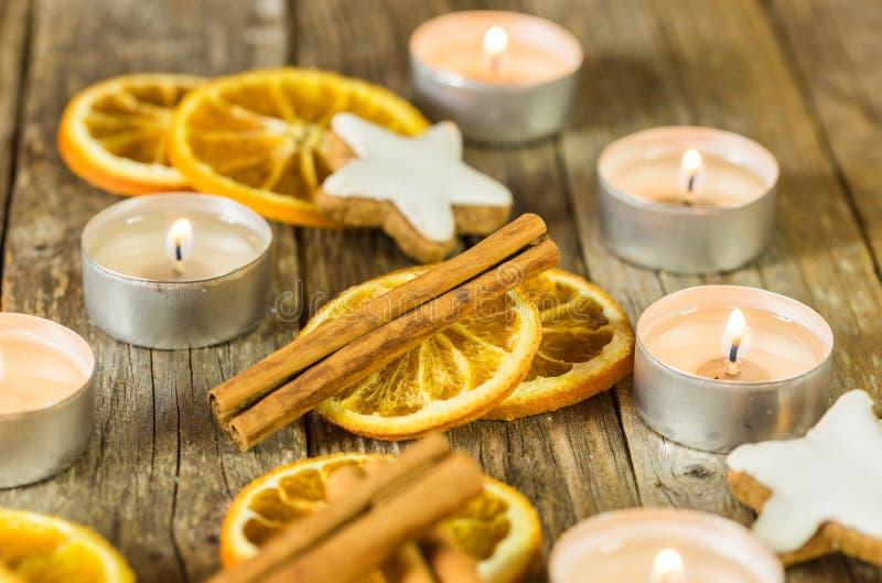 Decoração aromática da estação do Natal com velas ardentes, cookies da estrela, canela e fatias alaranjadas imagem de stock