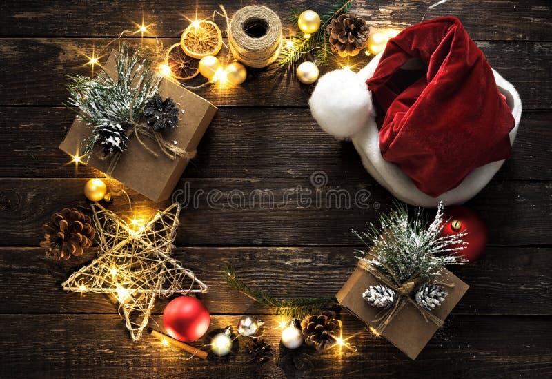 A decoração colocada lisa da grinalda do fundo do Natal ilumina a opinião superior do fundo de madeira escuro foto de stock