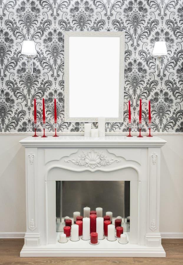 Decoração colocada sobre a chaminé: velas, lâmpada, modelo vazio da moldura para retrato Conceito do tema do ano novo e do Natal imagem de stock