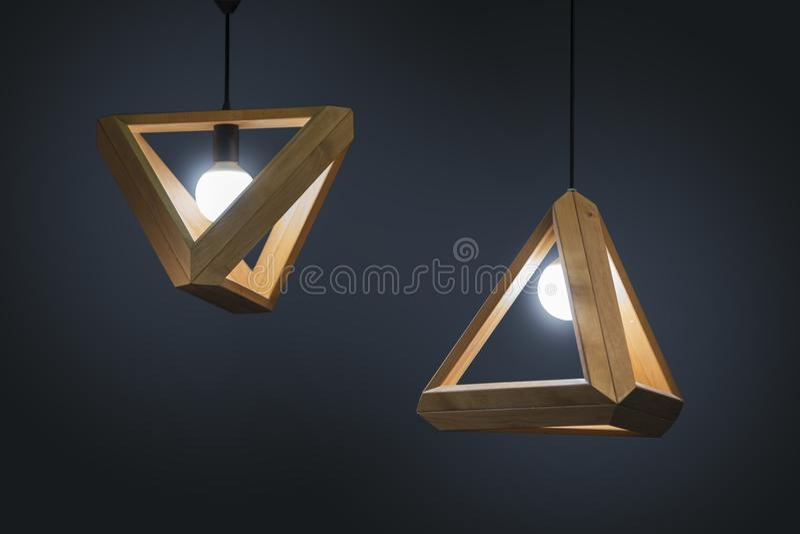 Decoração contemporânea interior da lâmpada moderna geométrica de madeira bonita do teto isolada em um fundo escuro imagem de stock royalty free