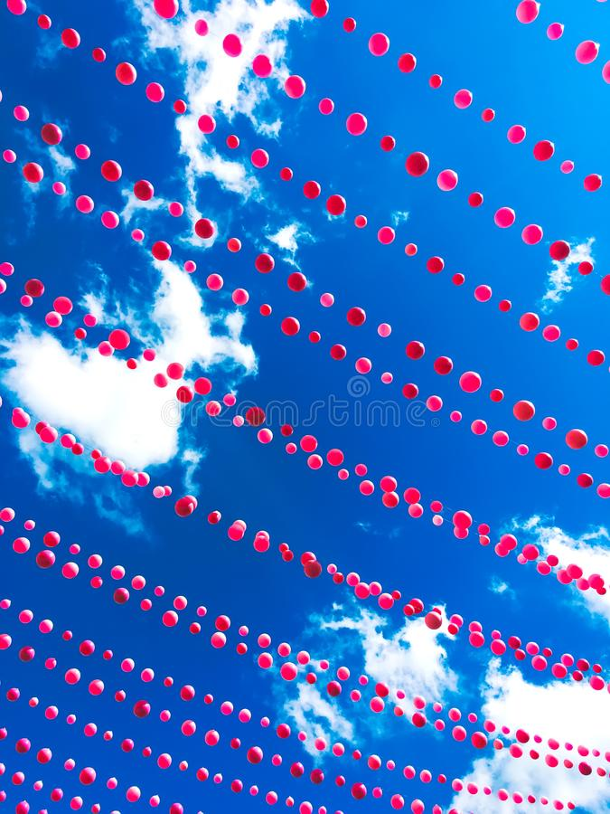 Decoração cor-de-rosa das bolas contra o céu azul e as nuvens foto de stock