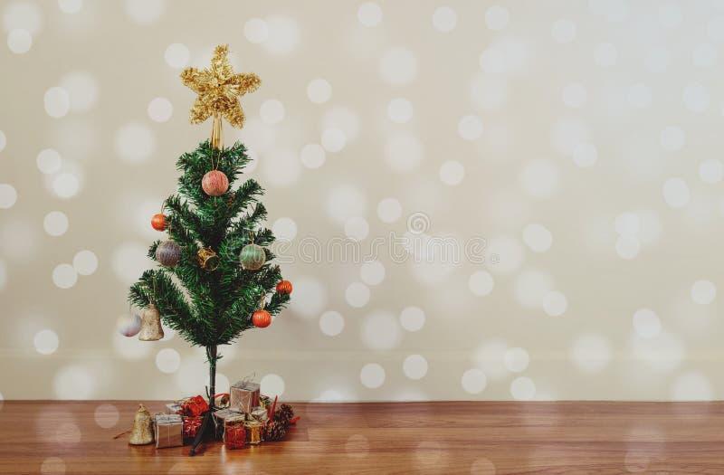 A decoração da árvore de Natal com círculo Bokeh ilumina-se no assoalho de madeira, na sala de visitas foto de stock royalty free