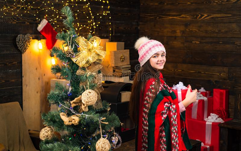Decoração da árvore de Natal O adolescente pequeno feliz no chapéu de Santa com atual tem um Natal Ano novo feliz Crianças do inv imagens de stock royalty free