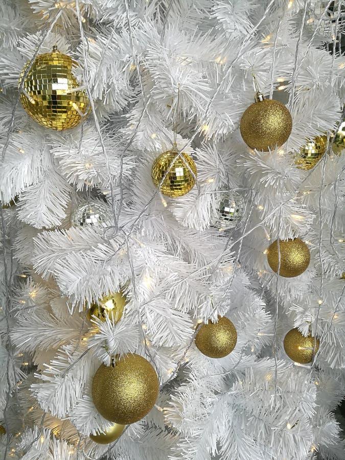 Decoração da árvore do White Christmas, variedade de ornamento de suspensão dourados da bola com ouropel branco foto de stock royalty free
