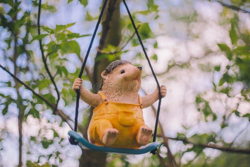 Decoração da estatueta do jardim do close-up - um ouriço alegre na roupa amarela que se senta em um balanço - que pendura em um r fotografia de stock