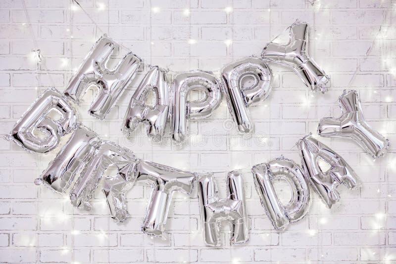 Decoração da festa de anos - as letras do feliz aniversario arejam balões sobre a parede de tijolo com luzes imagens de stock