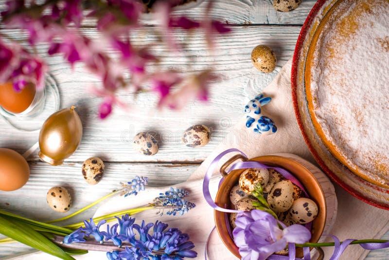 A decoração da Páscoa, as flores e a Páscoa alemão endurecem na tabela de madeira branca foto de stock