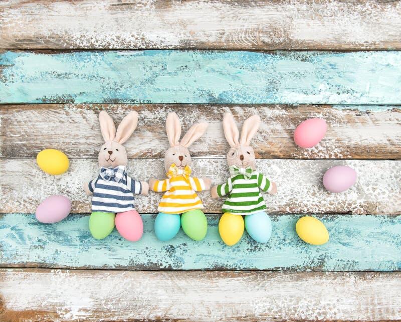 A decoração da Páscoa eggs o fundo de madeira dos coelhos engraçados foto de stock