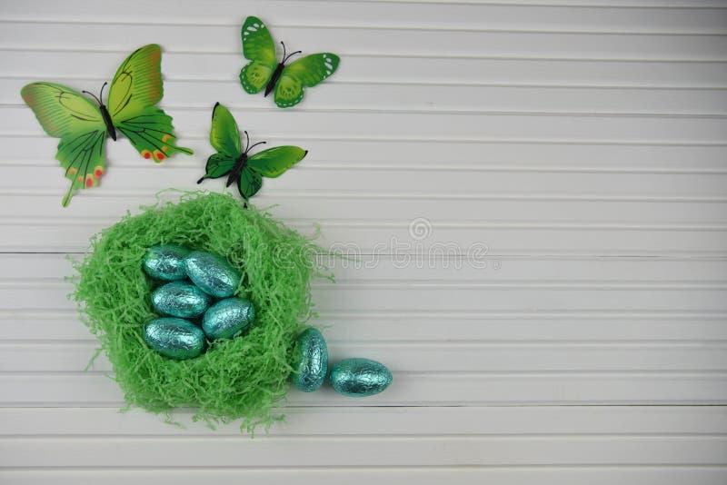 A decoração da Páscoa da primavera com o ninho feito a mão da cor verde encheu-se com os ovos da folha e as decorações brilhantes imagens de stock royalty free