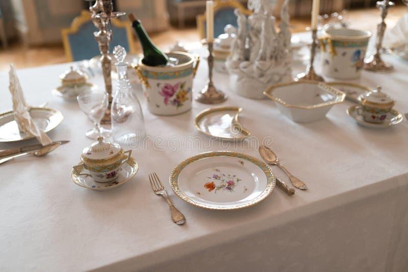 Decoração da tabela do casamento com as placas e a cutelaria reais retros caras do serviço da porcelana da majestade em um pal foto de stock royalty free