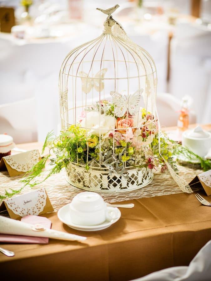 Decoração da tabela do casamento na profundidade rasa do restaurante do pássaro da gaiola do campo com flores para dentro fotos de stock royalty free