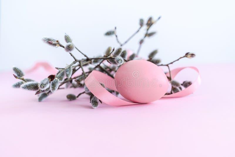 Decoração de domingo de palma do salgueiro de bichano com a fita cor-de-rosa do ovo da páscoa e a de seda no fundo cor-de-rosa imagem de stock