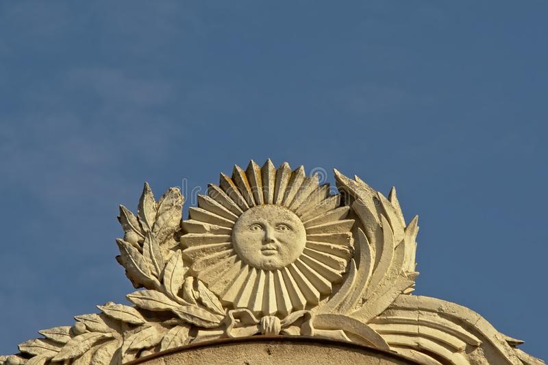 Decoração de pedra de um sol de sorriso cercado por um louro imagens de stock
