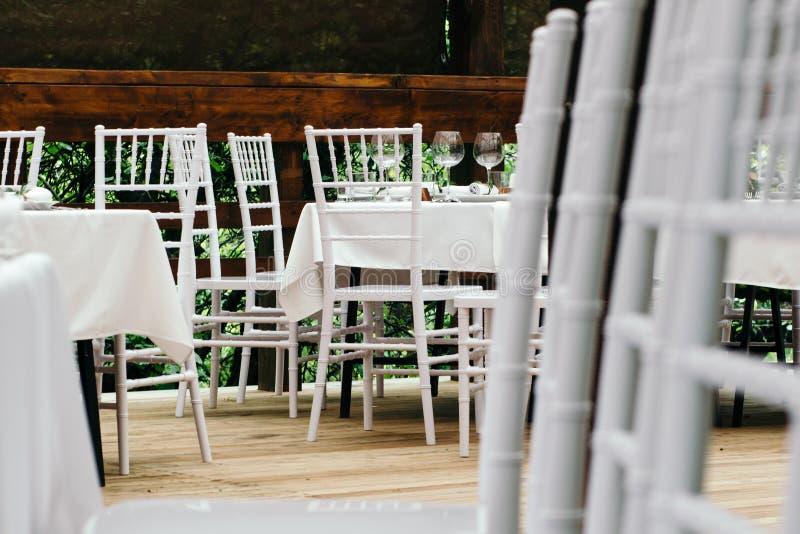 Decoração de vidro do casamento bonito na tabela Cadeiras de Chiavari na plataforma de madeira coberta imagem de stock