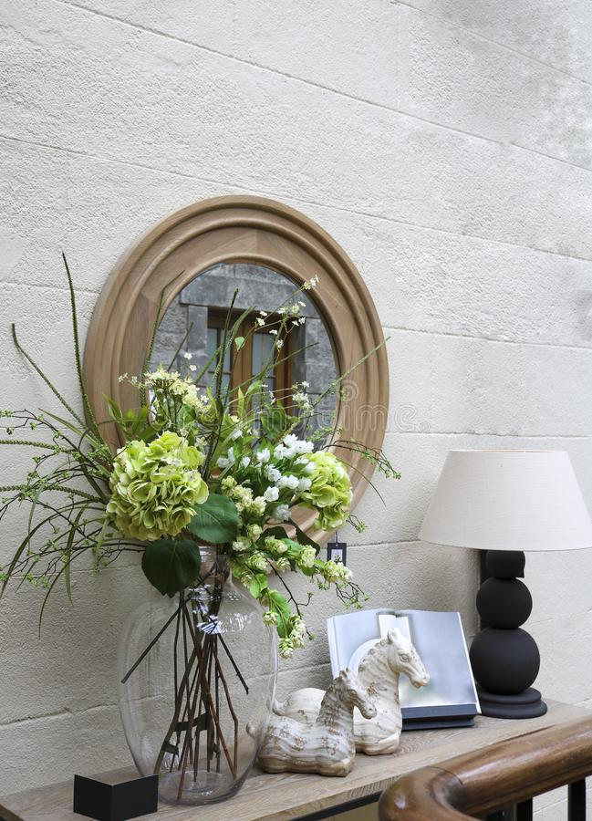 Decora??o decorativa da parede: um espelho, um console com uma l?mpada, flores e trinkets foto de stock royalty free