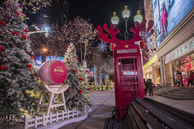 Decoração do ano novo do negócio, cabine de telefone vermelha roxa com chifres do chifre e árvore de Natal, opinião da noite fotografia de stock royalty free