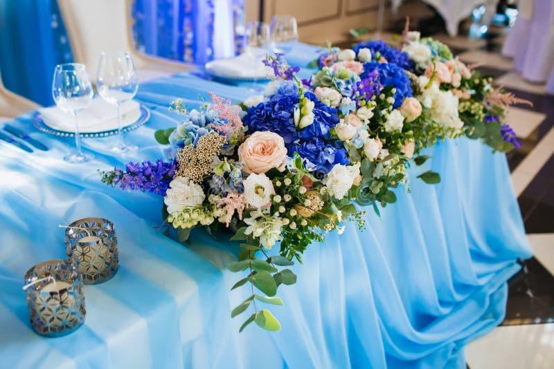 Decoração do banquete do casamento artwork Foco macio no ramalhete com eustoma e as hortênsias azuis em uma toalha de mesa azul foto de stock royalty free