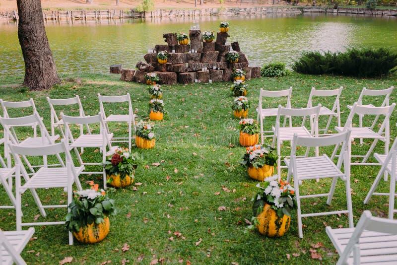 Decoração do casamento com abóboras e flores de outono Cerimônia exterior no parque Cadeiras brancas para convidados imagens de stock royalty free