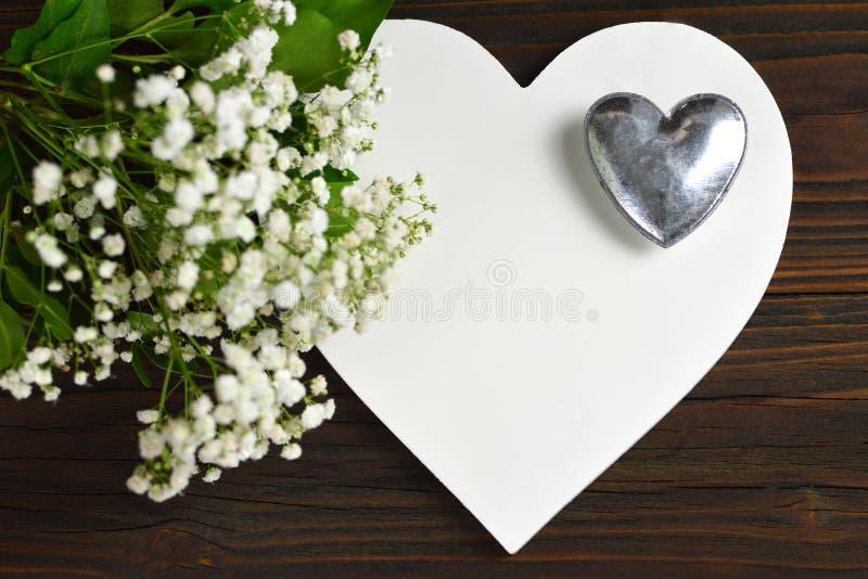 Decoração do casamento Coração branco e flores brancas na parte traseira de madeira imagens de stock