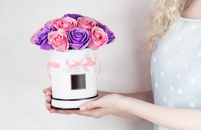 Decoração do casamento: a menina em um vestido do globo guarda uma caixa redonda com um ramalhete de cor-de-rosa, roxo, rosas da  imagens de stock royalty free