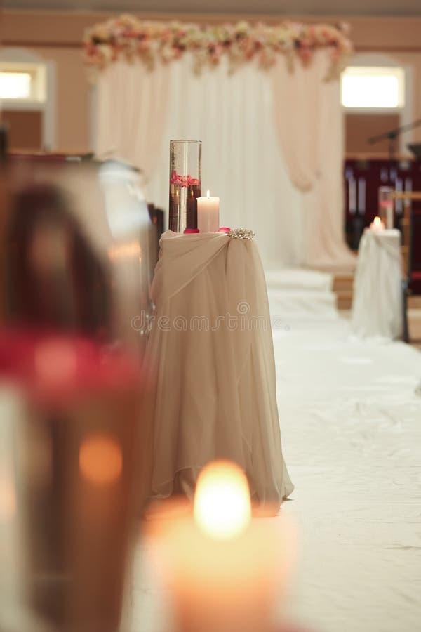 decoração do casamento um a vela e um vaso com água em uma tabela branca Garrafas com água e uma vela de flutuação imagens de stock royalty free