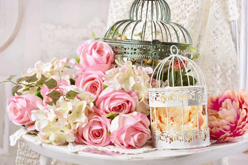 Decoração do estilo do vintage com as flores em gaiolas de pássaro velhas fotos de stock
