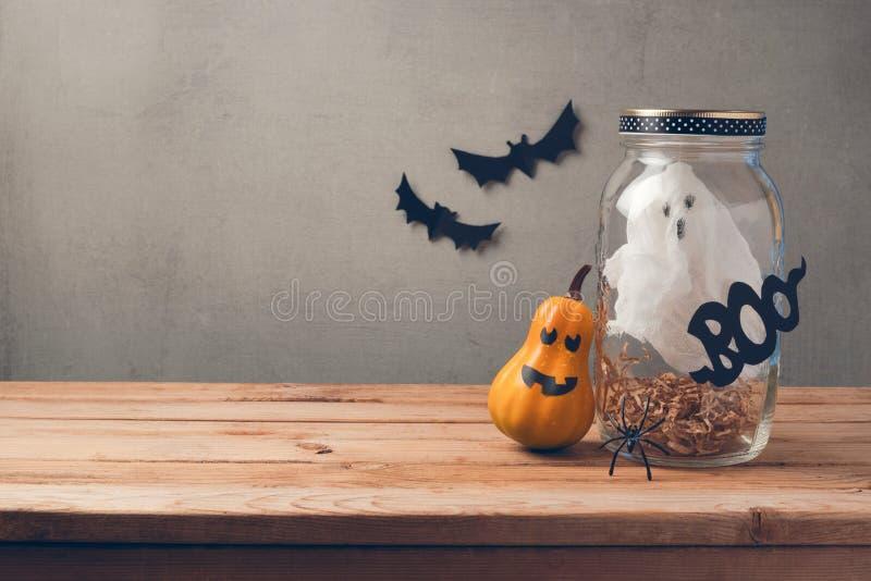 Decoração do feriado de Dia das Bruxas com o fantasma no frasco e na abóbora com a cara assustador na tabela de madeira imagens de stock royalty free