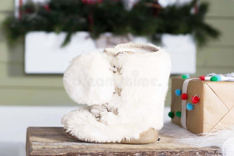 Decoração do inverno com a bota de neve branca e a caixa atual imagens de stock