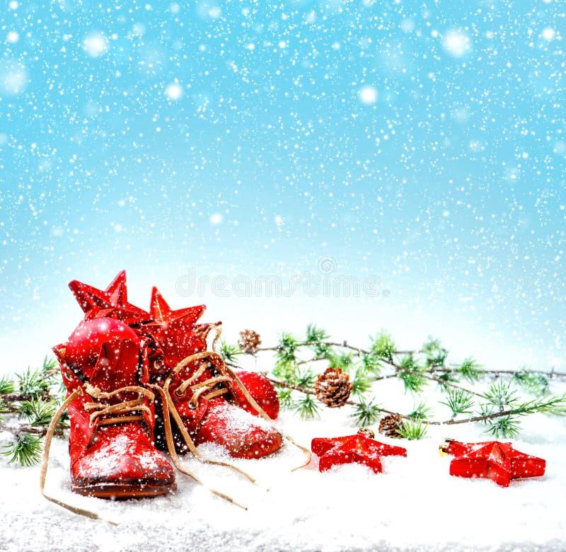 Decoração do Natal com as sapatas de bebê antigas efeito de queda da neve foto de stock royalty free