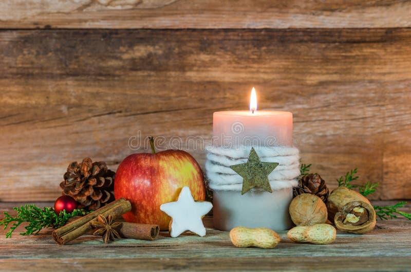 Decoração do Natal com luz da vela, cookie da estrela, as especiarias vermelhas da maçã, as nuts e as aromáticas foto de stock