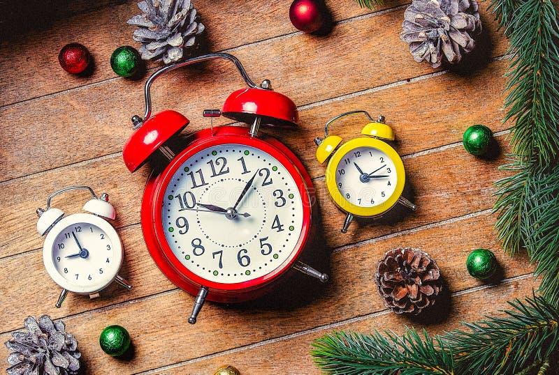 A decoração do Natal e os despertadores pequenos aproximam o ramo do pinho foto de stock