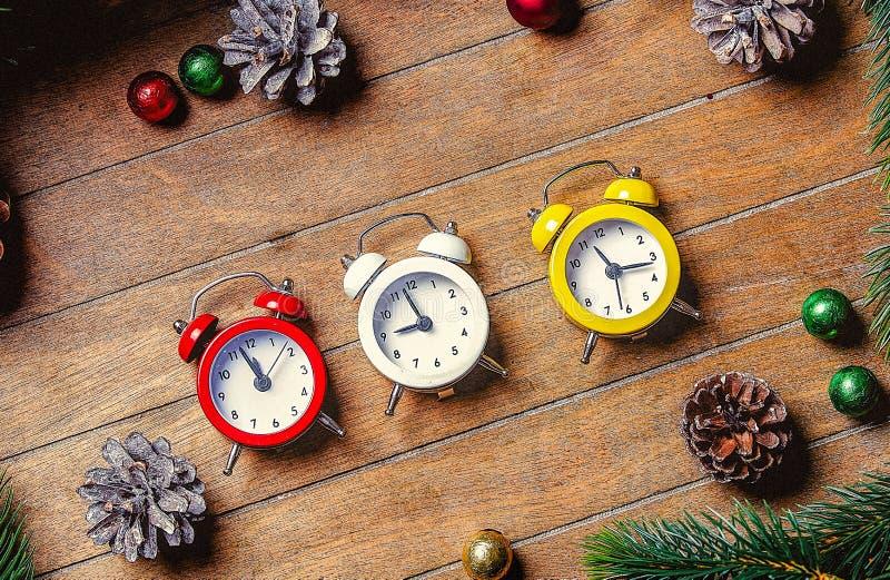 A decoração do Natal e os despertadores pequenos aproximam o ramo do pinho imagens de stock