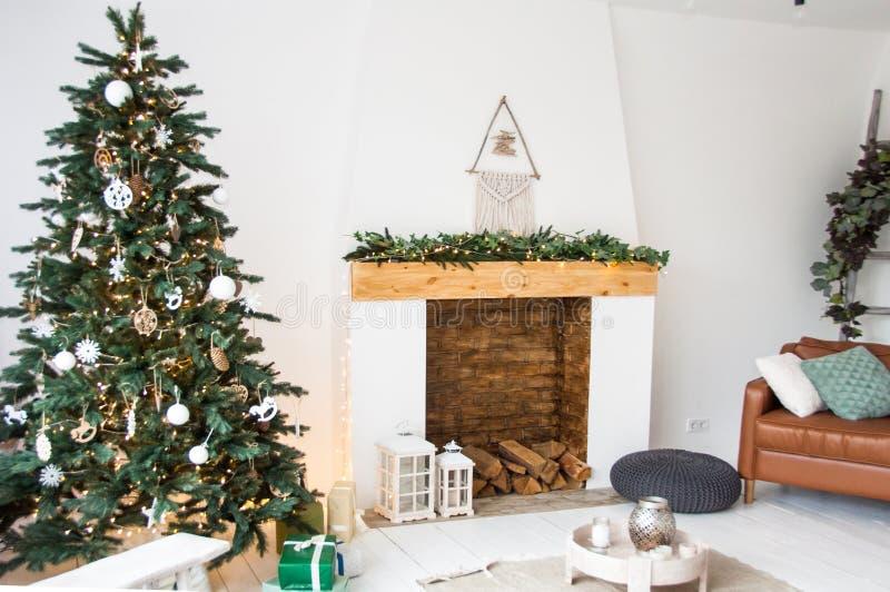 Decoração do Natal para a sala de visitas branca com a árvore da chaminé e de Natal, design de interiores imagem de stock royalty free