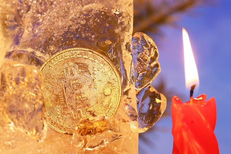 Decoração do ` s do ano novo Bitcoin afundado no gelo e iluminado pela chama de uma vela vermelha na perspectiva do Natal fotografia de stock