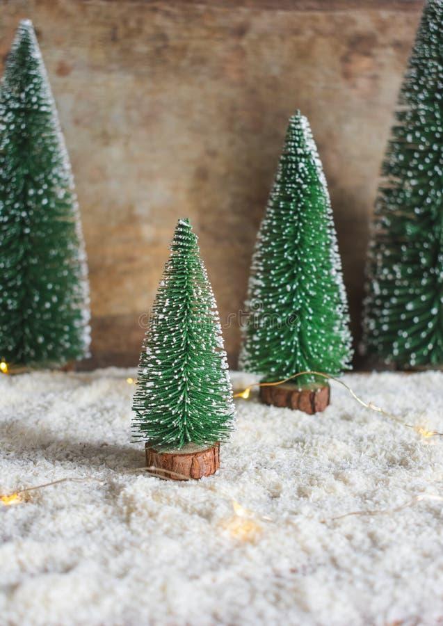 Decoração e luzes nevados verdes das árvores de Natal no fundo de madeira imagens de stock